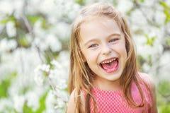 Glückliches kleines Mädchen im Kirschblütengarten lizenzfreie stockfotos