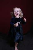 Glückliches kleines Mädchen im Partykleid mit Spielzeug Stockfoto