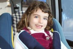 Glückliches kleines Mädchen innerhalb des Autosicherheitsstuhls Lizenzfreies Stockbild