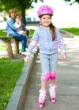 Glückliches kleines Mädchen läuft auf Rollen eis lizenzfreie stockfotografie