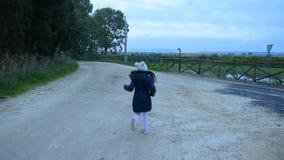 Glückliches kleines Mädchen läuft in einen bewölkten Tag stock footage