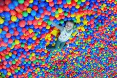 Glückliches kleines Mädchen legt auf den großen Haufen von mehrfarbigen Bällchen Stockbild
