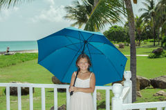 Glückliches kleines Mädchen mit blauem Regenschirm ihre Ferienzeit im gemütlichen tropischen Garten genießend Stockfotografie