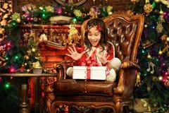 Glückliches kleines Mädchen mit dem Geschenkboxsitzen stockfoto
