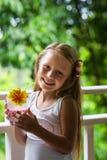 Glückliches kleines Mädchen mit dem langen Haar auf dem Balkon eines Erholungsortes morgens mit einem Glas Milch Lizenzfreies Stockfoto