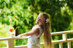 Glückliches kleines Mädchen mit dem langen Haar auf dem Balkon eines Erholungsortes morgens mit einem Glas Milch Lizenzfreie Stockfotos