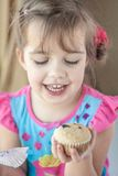 Glückliches kleines Mädchen mit einem Muffin Stockfoto