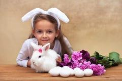 Glückliches kleines Mädchen mit ihrem Frühlingskaninchen und Saisonblumen Lizenzfreie Stockfotos
