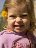 Glückliches kleines Mädchen mit Löwenzahn Stockfotografie