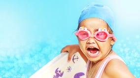 Glückliches kleines Mädchen mit netten Schwimmenschutzbrillen Stockfotos