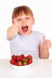 Glückliches kleines Mädchen mit Platte mit Erdbeeren stockfoto