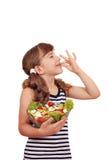 Glückliches kleines Mädchen mit Salat und okayzeichen Stockbilder