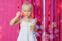 Glückliches kleines Mädchen mit Seifenblasen Stockbild