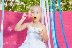 Glückliches kleines Mädchen mit Seifenblasen Stockbilder