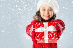 Glückliches kleines Mädchen mit Weihnachtsgeschenk auf Schneehintergrund Stockfotografie