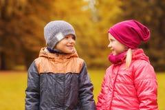 Glückliches kleines Mädchen und der Junge, die im Herbst spricht, parken Stockfoto