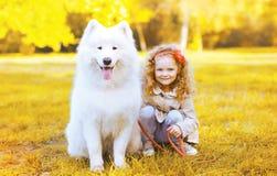 Glückliches kleines Mädchen und Hund, die Spaß im sonnigen Herbsttag hat Stockfotos