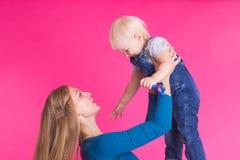 Glückliches kleines Mädchen und ihre Mutter, die Spaß über rosa Hintergrund hat lizenzfreie stockfotografie