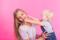 Glückliches kleines Mädchen und ihre Mutter, die Spaß über rosa Hintergrund hat lizenzfreies stockbild