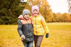 Glückliches kleines Mädchen und Junge im Herbst parken Lizenzfreie Stockfotos