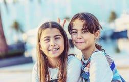 Glückliches kleines Mädchen zwei, das die Kamera lächelt und betrachtet Stockfotos