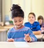 Glückliches kleines Schulmädchen über Klassenzimmerhintergrund Stockbild