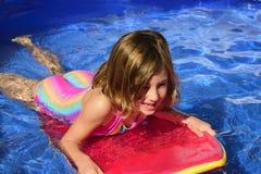 Glückliches kleines Surfermädchen mit Brandungsbrett Stockfoto