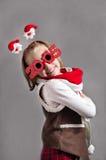 Glückliches kleines Weihnachtskindermädchen mit Gläsern 2015 Lizenzfreie Stockfotografie