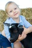 Glückliches Kleinkind, das ihre Ziege umarmt. Lizenzfreie Stockbilder