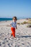 Glückliches Kleinkind, das mit dem Haar im Wind geht Lizenzfreies Stockfoto