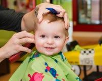 Glückliches Kleinkind, das seinen ersten Haarschnitt erhält Stockfotografie