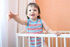 Glückliches Kleinkind im weißen Bett Stockfotos