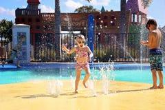Glückliches Kleinkind-Kind, das in den Wasser-Brunnen am Spritzen-Park springt und spielt lizenzfreies stockbild