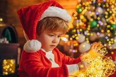Glückliches Kleinkind spielt mit Weihnachtslicht auf Weihnachtsbaumhintergrund Abschluss oben Frohe Feiertage Familie lizenzfreie stockfotografie