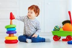 Glückliches Kleinkindbaby, das bunte Ringe auf Pyramide sortiert Lizenzfreies Stockbild