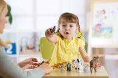 Glückliches Kleinkindmädchen Lächelndes Kinderkleinkind spielt Tierspielwaren zu Hause oder Kindergarten stockfoto