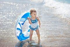 Glückliches Kleinkindmädchen mit aufblasbarem Kreis in Meer lizenzfreie stockfotos