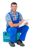 Glückliches Klempnerschreiben auf Klemmbrett beim Sitzen auf Werkzeugkasten Stockfotos