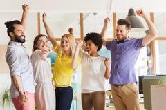 Glückliches kreatives Team, das Sieg im Büro feiert Stockbild
