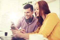 Glückliches kreatives Team mit Smartphones im Büro Lizenzfreie Stockfotografie