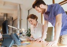 Glückliches kreatives Team mit Tabletten-PC im Büro Lizenzfreies Stockbild