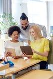 Glückliches kreatives Team mit Tabletten-PC im Büro Stockfotografie