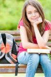 Glückliches Kursteilnehmermädchen, das auf Bank mit Buch sitzt Lizenzfreie Stockfotos