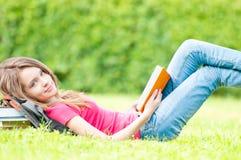 Glückliches Kursteilnehmermädchen, das auf Gras mit geöffnetem Buch liegt Lizenzfreies Stockfoto