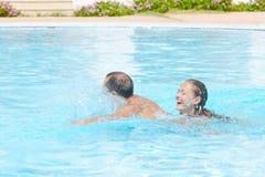 Glückliches Lächeln bei der Entspannung am Rand eines Schwimmbads lizenzfreie stockfotografie