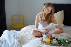 Glückliches Lächeln blond im weißen Bett Lizenzfreie Stockfotos