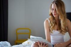 Glückliches Lächeln blond im weißen Bett Stockbild