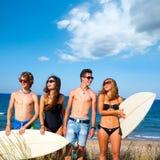 Glückliches Lächeln der jugendlich Surfer der Jungen und der Mädchen auf Strand Lizenzfreies Stockfoto