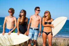 Glückliches Lächeln der jugendlich Surfer der Jungen und der Mädchen auf Strand Lizenzfreie Stockfotos