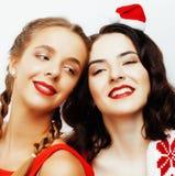 Glückliches Lächeln der Junge recht blond und Brunettefrauenfreundinnen auf Weihnachten in rotem Hut Sankt und Feiertag verziert Lizenzfreie Stockfotografie